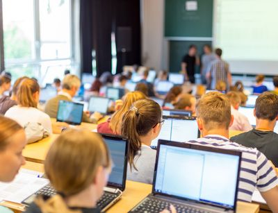 Students in a lecture hall with laptops at a lecture